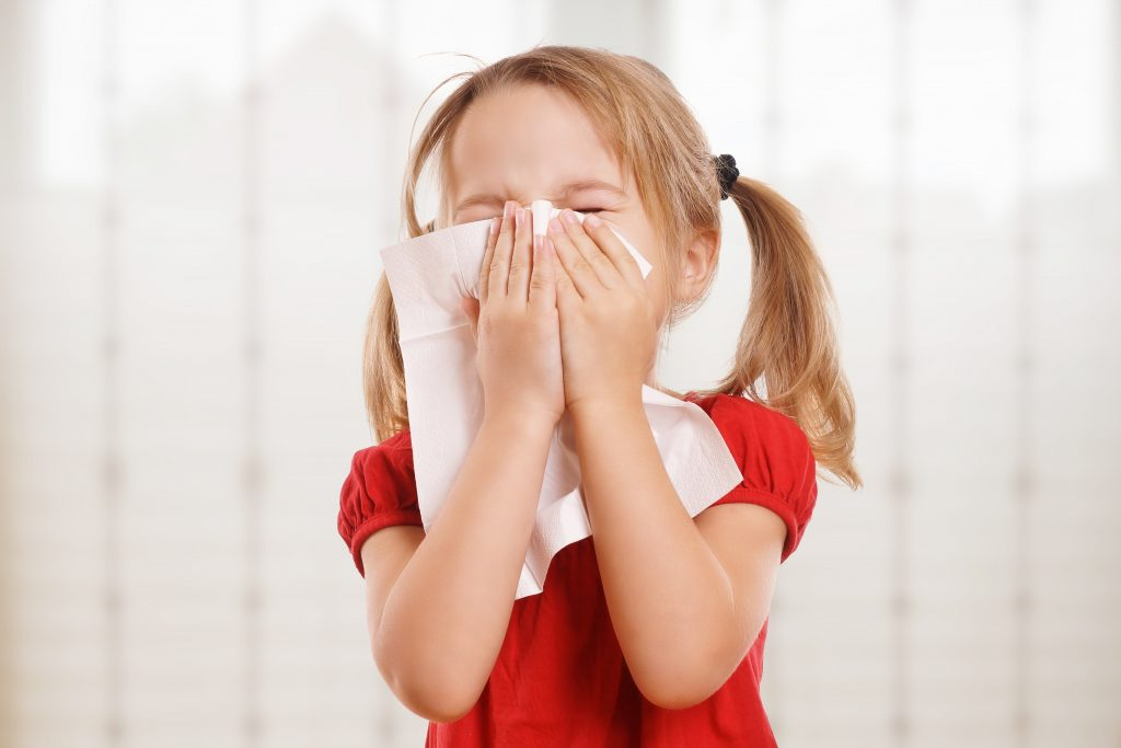 little girl with pigtails and red shirt sneezing into Kleenex.