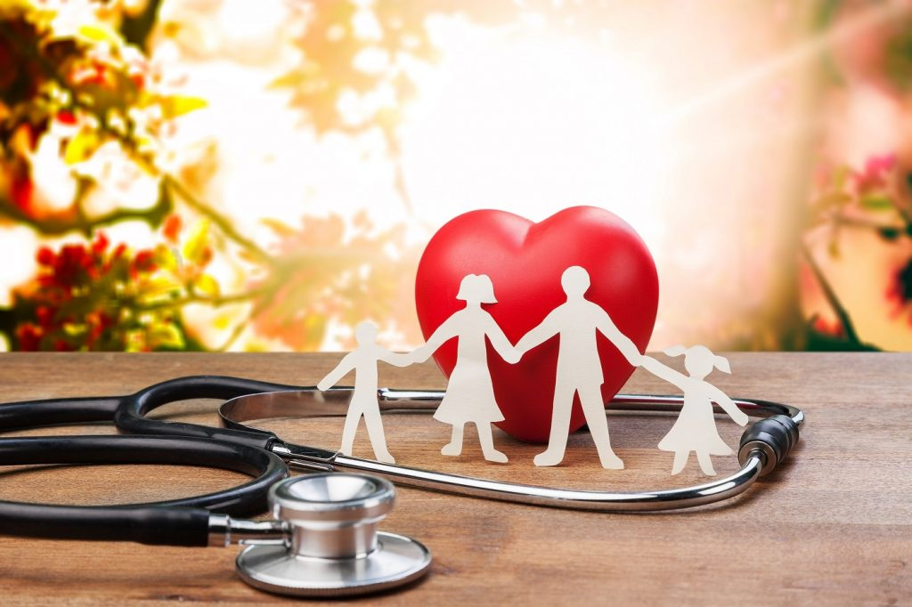 white cutout family in front of a model heart with a stethoscope surrounding them on a table