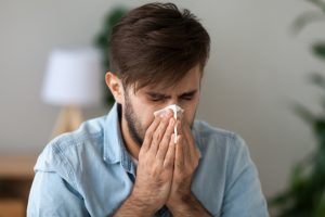 Sick man got flu grippe or allergy sneezing in handkerchief blowing wiping running nose, ill allergic guy caught cold coughing in tissue, having seasonal flu symptoms,