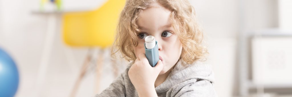 a young girl with asthma, a chronic illness, inhaling from an inhaler