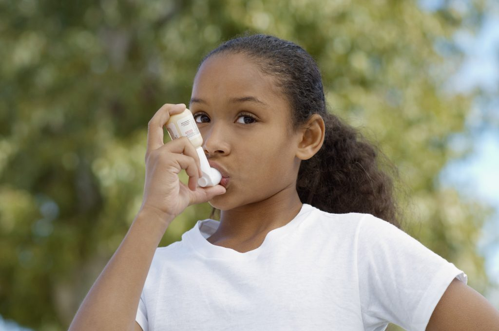 A young girl using her inhaler