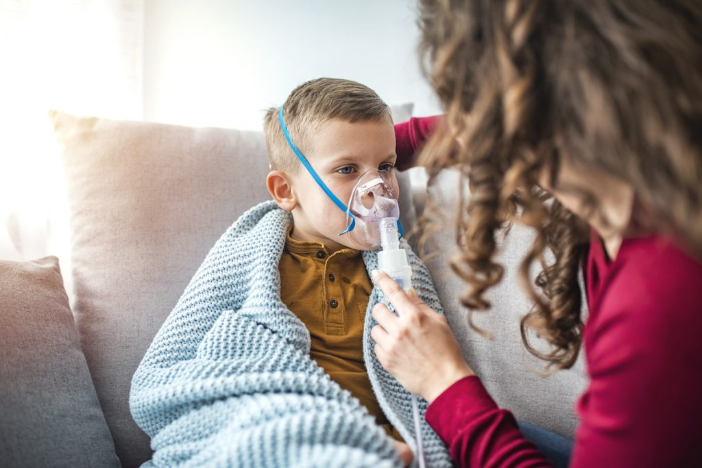 Woman with son doing inhalation with nebulizer at home. Causian little boy making inhalation with nebulizer. Child having respiratory illness helped by mother with inhaler