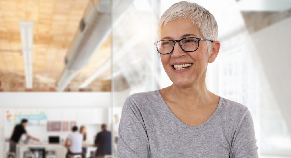 An older woman smiling after receiving hormone replacement therapy to treat her menopause symptoms