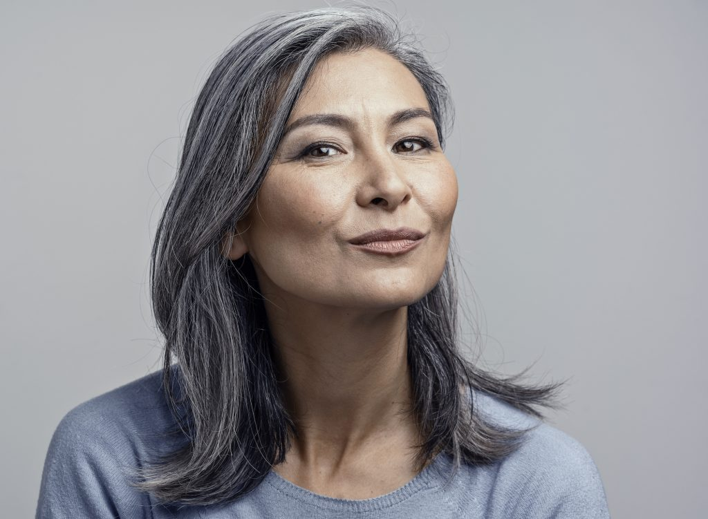 Charming Woman With Grey Hair With Delicate Smile. Portrait Of Pretty Middle-Aged Woman Making Duck Face While Smiling.
